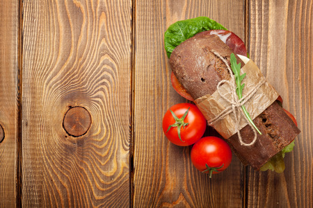 Sandwich with salad, ham, cheese and tomatoes on wooden table. Top view with copy space photo