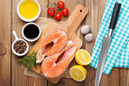 Salmon and spices on wooden table. Top view photo