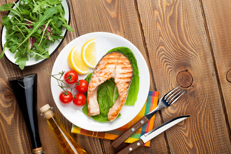 meat dish: Grilled salmon, salad and condiments on wooden table. Top view with copy space
