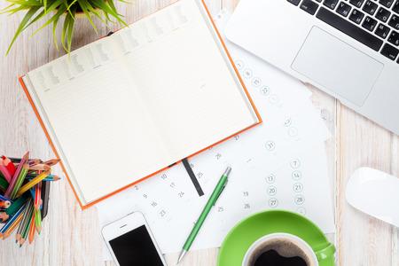 コンピューター、用品、コーヒー カップ、花とオフィス デスク テーブル。コピー スペース平面図 写真素材
