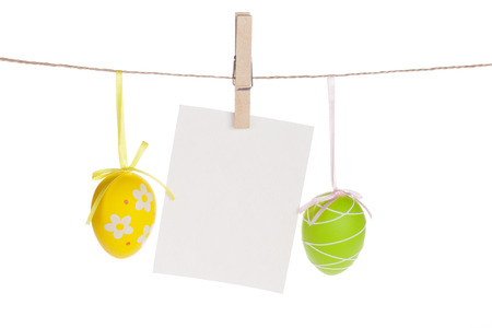 clothespin: Colorful easter eggs and blank photo frame hanging on rope. Isolated on white background Stock Photo