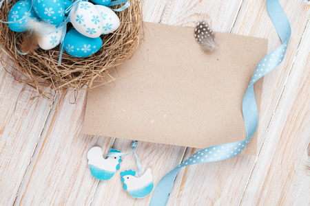 easter nest: Easter greeting card with blue and white eggs in nest and decor. Top view with copy space Stock Photo