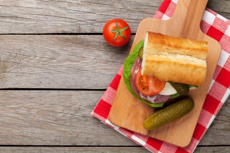 나무 테이블에 샐러드, 햄, 치즈, 오이, 토마토 샌드위치. 복사 공간 상위 뷰