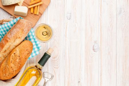 pan frances: Vino blanco, queso y pan en blanco de madera fondo de la tabla. Vista superior con espacio de copia