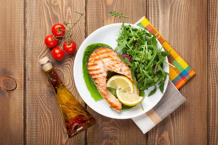 alimentacion sana: Salmón a la parrilla, ensalada y condimentos en la mesa de madera. Vista superior