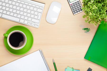 コーヒー カップ、コンピューターおよび花とのオフィスのテーブル。コピー領域の上からの眺め