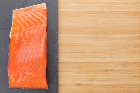 red  stone: Fresh salmon fish on bamboo wooden table with copy space