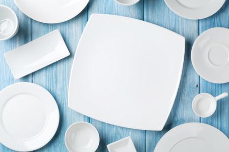 Leere Teller und Schüsseln auf blauem Holzuntergrund. Ansicht von oben mit Kopie Raum