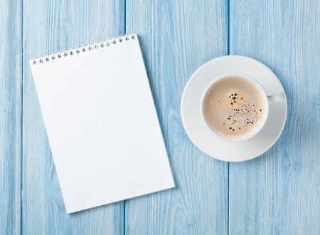 Coffee cup and blank notepad over blue wooden table. Top view with copy space Stockfoto