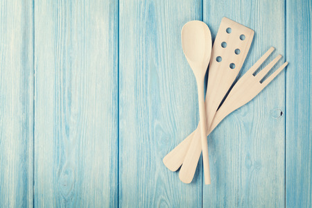 blue toned: Kitchen cooking utensils over wooden table background. Top view with copy space. Retro toned