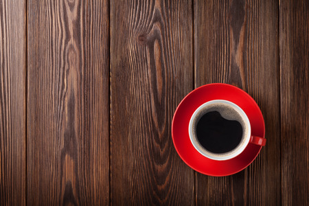 red: Coffee cup on wooden table background. Top view with copy space Stock Photo