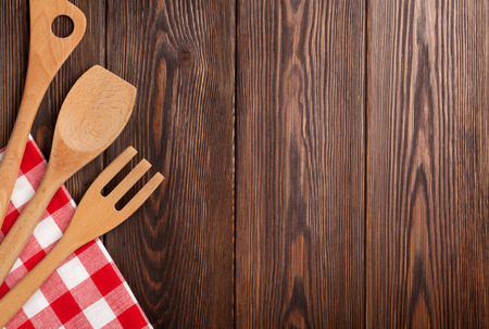 Kitchen cooking utensils over wooden table background. Top view with copy space