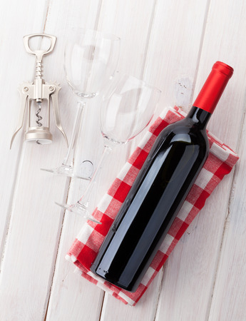 Red wine bottle, glasses and corkscrew on white wooden table background