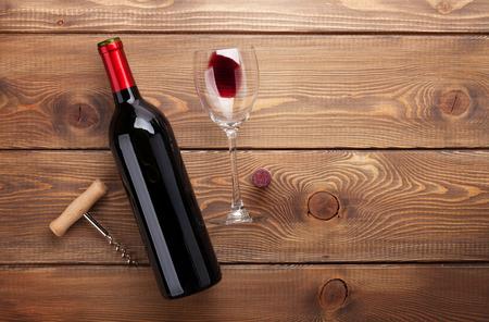 Red wine bottle, glass of wine and corkscrew. View from above over rustic wooden table background with copy space photo