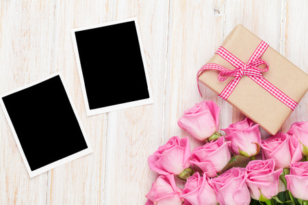 two on top: Pink roses and valentines day gift box and two blank photo frames over wooden table. Top view with copy space