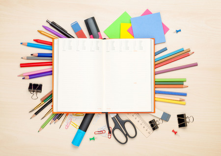 office stationery: Blank notepad over school and office supplies on office table. Top view with copy space