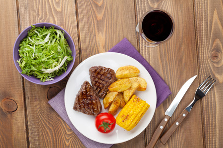 grilled potato: Steak with grilled potato, corn, salad and red wine over wooden table. Top view Stock Photo