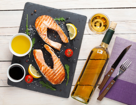 salmon steak: Grilled salmon and white wine on wooden table. Top view