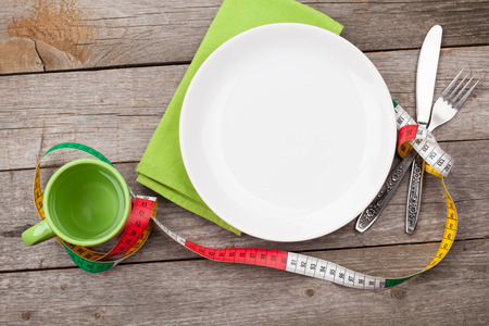 Plate with measure tape, cup, knife and fork. Diet food on wooden table photo