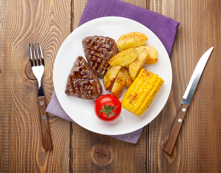 grilled potato: Steak with grilled potato, corn and salad on wooden table. Top view Stock Photo