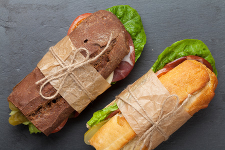 sub sandwich: Two sandwiches with salad, ham, cheese and tomatoes on stone table Stock Photo