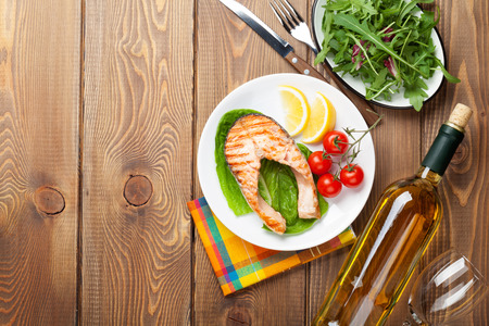 fish dinner: Grilled salmon and white wine on wooden table. Top view with copy space Stock Photo