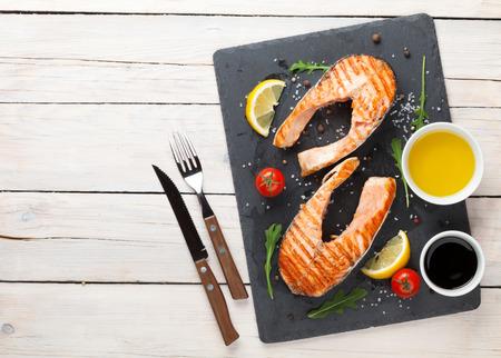 サーモンのグリル、サラダ、木製のテーブルの上の調味料。コピー スペース平面図