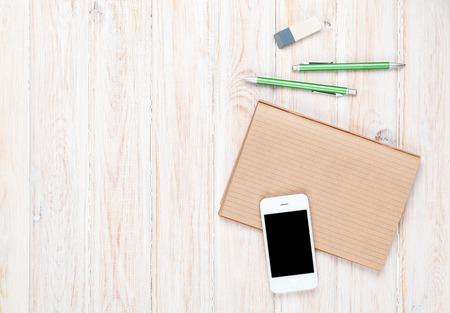 Bureau tafel met voorraden en smartphone. Bovenaanzicht met een kopie ruimte