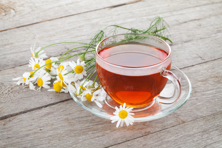 chamomile tea: Herbal tea with chamomile flowers on wooden table background