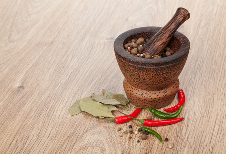 Mortar and pestle with red hot chili pepper and peppercorn on wooden table photo