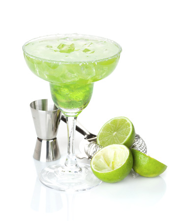 margarita drink: Classic margarita cocktail with salty rim with limes and drink utensils. Isolated on white background