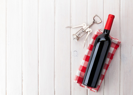 Red wine bottle and corkscrew on white wooden table background with copy space Foto de archivo