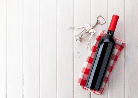 Láhev červeného vína a vývrtka na bílém dřevěném stole pozadí s kopií vesmíru