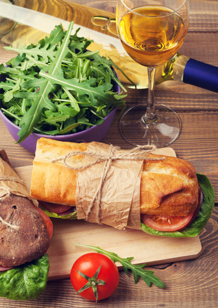 ham sandwich: Two sandwiches and white wine glass on wooden table