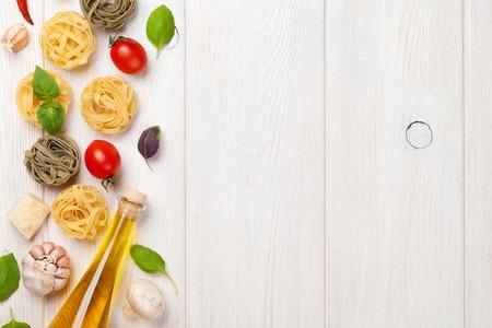 pastas: Ingredientes para cocinar la comida italiana con pasta, tomates, albahaca. Vista superior con espacio de copia