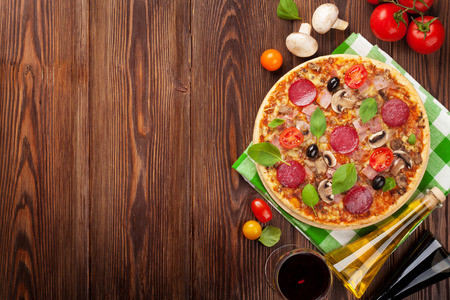 Pizza and red wine on wooden table background. Top view with copy space