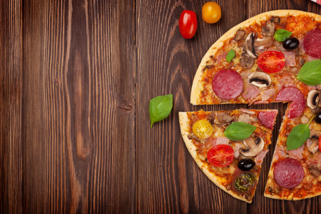 pizza: Pizza italiana con pepperoni en mesa de madera. Vista superior con espacio de copia