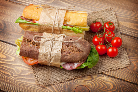 Two sandwiches with salad, ham, cheese and tomatoes on wooden table. Top view