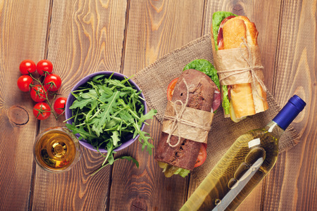 Two sandwiches, salad and white wine on wooden table. Top view. Toned photo