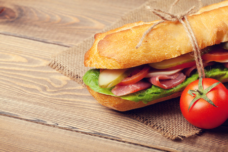 Sandwich with salad, ham, cheese and tomatoes on wooden table Stock Photo