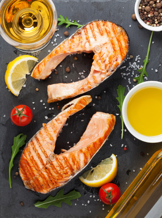 red  fish: Grilled salmon and white wine on stone board. Top view Stock Photo