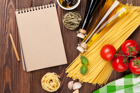Italian food cooking ingredients. Pasta, tomatoes, basil. Top view with notepad for copy space Stock Photo