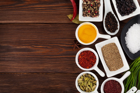 kitchen background: Various spices on wooden background. Top view with copy space