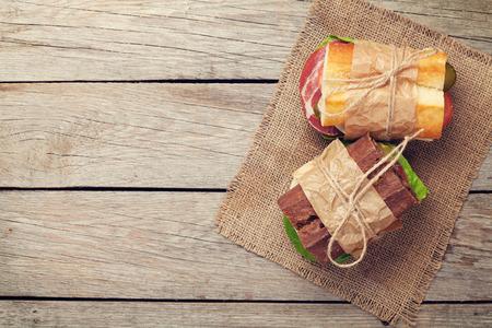 bocadillo: Dos emparedados con ensalada, jamón, queso y tomates en mesa de madera. Vista superior con espacio de copia