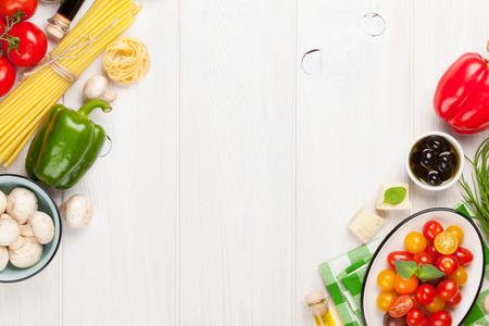 cocinando: Ingredientes para cocinar la comida italiana. Pasta, verduras, especias. Vista superior con espacio de copia Foto de archivo