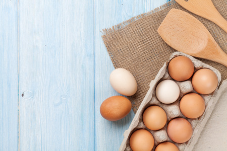 product range: Cardboard egg box on wooden table. Top view with copy space Stock Photo