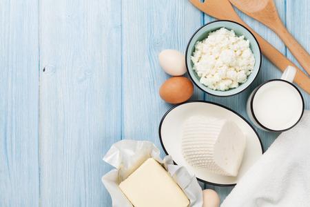 dairy: Productos lácteos en la mesa de madera. Leche, queso, huevos, requesón y mantequilla. Vista superior con espacio de copia