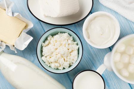 木製テーブルの上の乳製品。サワー クリーム、牛乳、チーズ、卵、ヨーグルト、バター。トップ ビュー