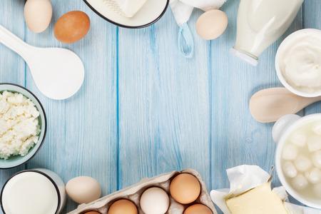 leche y derivados: Productos lácteos en la mesa de madera. Crema agria, leche, queso, huevos, yogur y mantequilla. Vista superior con espacio de copia Foto de archivo