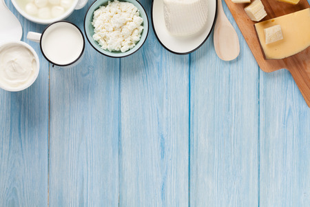 yogur: Productos lácteos en la mesa de madera. Crema agria, leche, queso, huevos, yogur y mantequilla. Vista superior con espacio de copia Foto de archivo